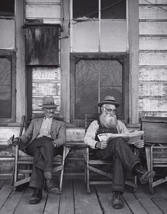 1934 Two Men on Porch, Hornitos [two men with hats sitting on weathered porch, one on right reading newspaper] by Ansel Adams 76.83.39