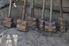 """Making Rammed Earth Walls """"Prior to the compaction, the mould is filled with slightly moist soil up to a layer height of between 8cm to 15cm. To compact the soil, we traditionally use a stamper that consists of a heavy foot (between 3kg – 8kg of steel, wood or stone) and a handle."""""""