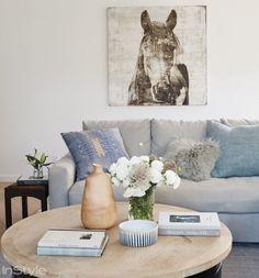 Inspiração de decor direto de Hollywood: a casa da atriz Lea Michele. A sala de estar é simples porém elegante, com sofá cinza, mesa de centro de madeira e parede branca.