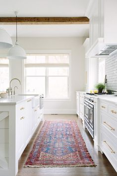white kitchen with colorful rug and wood beam accents
