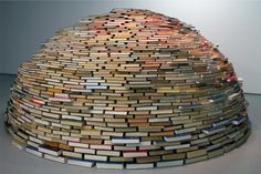 """Igloo"" by Colombian artist Miler Lagos is a 9-foot domed sculpture composed of layers of books. The outer white shell consists of the books' paper pages, while the inside reveals colorful bindings from a selection of foreign language dictionaries, medical reference series, geographical studies, and psychology volumes, all laid like bricks in a cylindrical shape."