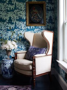A timeless ivory wingback chair adds contrast to the blue and white wallpaper, Chinoiserie-inspired garden stool and navy accent pillow in this chic corner.