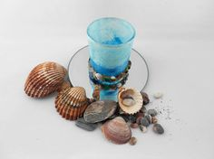 A lovely beach tealight holder hand decorated with straw silk fibre papers in blue and pale blue, the bottom is decorated with shells, pebbles and sand, the paper has a lovely shimmer with the aid of a metallic finish, this has been sealed to protect the finish..  You have the choice of a mirror plate or a glass plate please see options  Please note that this is a handmade item An attractive ornamental piece which gives a soft ambient glow when lit, this would make an ideal gift. It comes…