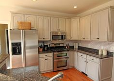cool-baltic-brown-granite-with-white-cabinets and white subway tile backsplash