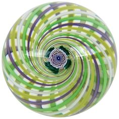 John Deacons studio glass paperweight with a swirl design in purple, green, yellow and white surrounding a Clichy-style rose.