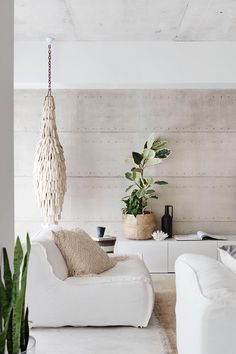 A rammed-earth feature wall, by Lime St Projects, runs the length of the eastern side of the house. Coffee table, sofachair, side table, cushions and white plant pots, all from Blupeter Homestore. **Designer buy:** Leaf Pod ceramic chandelier, $5200, Blupeter Homestore.