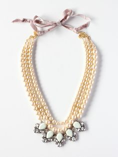 "Pearl & Rhinestone Statement Necklace: This stunning statement necklace features a lovely triple strand of graduated glass pearls that are accentuated by sparkling resin rhinestones. The necklace is 19"" in length and is finished with a beautiful 18-karat gold plated brass and velvet ribbon closure."