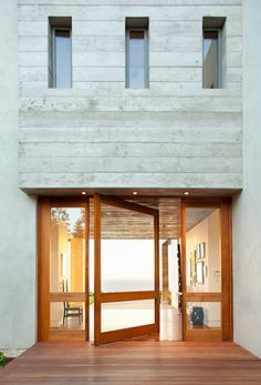 wood and glass pivot door at 7377 Birdview Residence by Burdge & Associates Architects