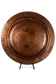 """From the best-selling IMAX Signature Collection comes this copper-plated charger with stand. Grand in scale, this piece is handmade with a beautiful hammered texture and heat applied finish and fits snugly into the custom iron stand.  The charger measures approximately 25"""" in diameter.  Because each piece is hand crafted, variations in color should be expected- each piece is unique!     Not for food use.                             Grand Copper Charger-With-Stand by IMAX Worldwide. Home…"""
