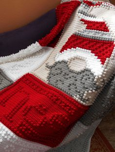 Make the house feel festive or give as a gift, this blanket design is easy to complete. The entire blanket requires only three crochet stitches - chain stitch, single crochet and the popcorn stitch. Christmas Crochet Blanket, Christmas Crochet Patterns, Holiday Crochet, Crochet Ornaments, Beginner Crochet Projects, Crochet For Beginners Blanket, Crochet Blanket Patterns, Crochet Blankets, Crochet Afghans