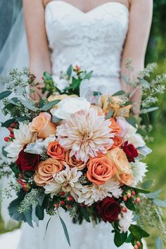 Shuttergram Photography | Gorgeous Bridal Bouquet Featuring: Café Au Lait Dahlias, Peach Roses, Orange Roses, Red Roses, Coral Hypericum Berries, Dusty Miller + Green Seeded Eucalyptus