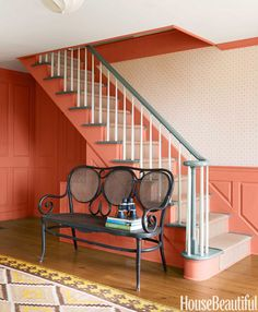 The original Thonet bench is like a sculpture and serves as a much-needed catchall. Stairwell in Farrow & Ball's Red Earth, with balusters in Benjamin Moore's Linen White.
