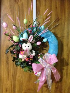 This adorable stuffed Easter bunny is peeking out from behind a beautiful combination of silk flower stems & Easter eggs with a wired ribbon bow. Would make a charming addition to anyones door. Measures approx. 18 x 18 x 6. Boxed and ready for shipping. Ribbons may be tucked around