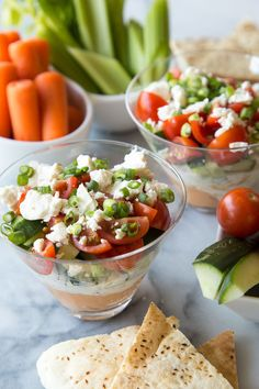 Five layer Mediterranean Dip with hummus, tzatziki, chopped cherry tomatoes, chopped cucumbers and feta cheese! It's easy, delicious and healthy! I'm all about a great party. Gathering my friends together is quite possibly my favorite activity and it always has to involve great food. These Five Layer Mediterranean Dip cups are an easy way to get appetizers out to your party without having to do much prep work!  Vegetarian