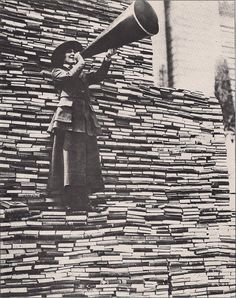 1910s. Standing on a mountain of already donated volumes, an amiable barker calls for still more books from passers-by outside the New York Public Library on Fifth Avenue.