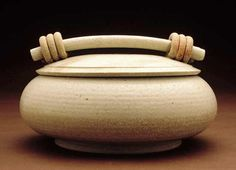 White Casserole by Jan Schachter. The unusual triple-coil handle is this artist's signature. High-fired *wheel-thrown:wheel thrown* and hand-built stoneware with a white ash *glaze*. Dishwasher and microwave safe; not oven safe.