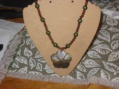 This is a very pretty brown and green necklace with a flower pendant that is black shell. the necklace is 19 3/4 long and the pendant is about 2 in wide.
