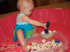 But the sensory bin inside a pool for babies to contain the mess!