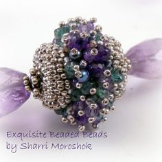Cover a wood base bead with glass seed beads.as a base for a dense layer of gemstone spikes tipped with tiny seed beads.  App. 1""