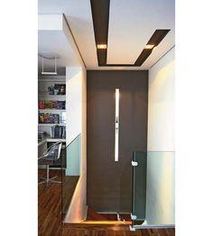 O segundo pavimento deste dúplex é marcado pelo rasgo no formato de U, que toma todo o forro do ambiente. Internamente, a fenda recebeu tinta no tom de concreto, aplicado também na parede da escada. A intenção desse desenho e da cor foi criar um foco de interesse no teto. A iluminação é proporcionada por halógenas AR-70, que se somam à luminária vertical da parede, cujo design esguio remete ao do recorte de gesso. Projeto de Cristiana Castro.