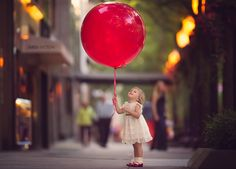 toddler girl holding a giant red balloon by Meg Bitton