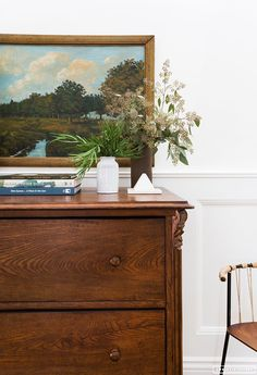 fabulous vignette with art by Amber Lewis, Amber Interiors - antique oak chest - oil painting - table styling - white walls with wainscoting. Amber has such a fresh, modern-traditional look