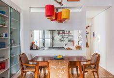 Sala de jantar com móveis de madeira e cozinha integrada.