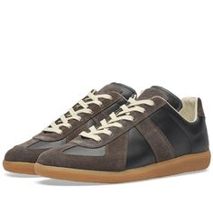 Currently helmed by British designer John Galliano, Maison Margiela continues to celebrate the quality of imperfection. This low top version of the Classic Replica is a re-imagining of a German track classic from the 70s and 80s. One of the brand's signature styles, this high-top sneaker boasts leather and suede uppers sat atop a classic gum sole unit. Finished to the highest level, the Replica features a full lambs leather lining, with the brand's iconic stitch at the heel.  100% Nappa…