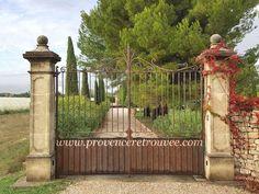 Paire de pilier en pierre avec chapiteau à boule et portail en fer avec volutes posés dans le vaucluse