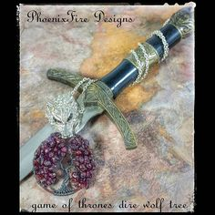 One of a kind!!  Handmade and wire wrapped in gunmetal wire with natural #garnet gemstones. Silver dire wolf head grips the tree in his mouth and pendant dangles from a finished chain.   ONE OF A KIND.  by phoenixfiredesigns