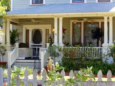 The vintage screen door, double columns, railing safety gate and homey decor make this front porch an extension of the home! Front-Porch-Ideas-and-More.com #porch