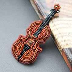Купить или заказать Брошь из бисера 'Скрипка' в интернет-магазине на Ярмарке Мастеров. Брошь ручной работы в виде скрипки - миниатюрная, но при этом насыщенная деталями работа. Я старалась сделать ее максимально похожей на оригинальный музыкальный инструмент, поэтому у маленькой скрипочки есть и колки, и эфы, и четыре струны, и даже маленький 'завиток', украшенный кристалликом Swarovski. Вся вышивка выполнена мелким японским бисером и рубкой, также в работе я использовала гран...