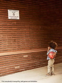 "Just a kid puzzled by a ""ball games forbidden"" sign"