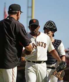 San Francisco Giants manager Bruce Bochy, left, greets closing pitcher Santiago Casilla, center, and Andrew Susac, right, at the end of a baseball game against the Colorado Rockies, Thursday, Aug. 28, 2014, in San Francisco. San Francisco won the game 4-1. (AP Photo/Eric Risberg)