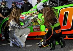 NASCAR Sprint Cup Series driver Danica Patrick (R), of the number 10 car, helps Miss Coors Light, Rachel Rupert, in securing a pole winner sticker on her car as she celebrates securing the pole position for the upcoming Daytona 500, during qualifying for the Daytona 500, at Daytona International Speedway in Daytona Beach, Florida, February 17, 2013.