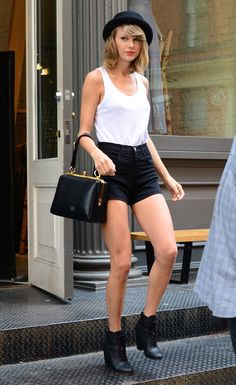 Taylor Swift looked so stylish rocking a white tank top, high waisted shorts and a cute bowler hat while out shopping in New York City. Her black ankle boots and black and gold handbag give her look a totally edgy vibe.