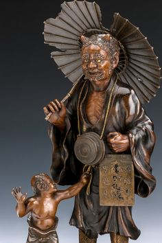 A lovely Japanese bronze figure group of a mendicant oni with a tattered umberella and wearing a voluminous cloak over tiger mask greaves, a smaller oni wears similar greaves and a loin cloth, set on a decorated wooden stand.http://richardgardnerantiques.co.uk/product/5403/JAPANESE+BRONZE+ONI+GROUP