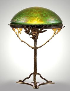 An Art Nouveau iridescent glass and brass table lamp attributed to Loetz, Austria circa 1900