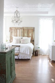 eclectic bedroom by Dreamy Whites. This room is the closest . . .  to the original Shabby Chic style. Its aesthetic is spare, which lets its weathered pieces, crystal chandelier and weathered-door headboard stand out.