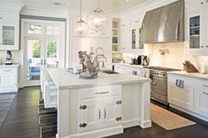 A modern vintage kitchen featuring white cabinets and countertops, dark tile flooring, glass globe pendant lights and a very large island with a sink an lots of seating - White Kitchen Ideas & Decor