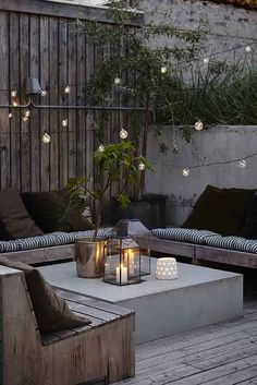 Black and grey garden nook with a roof top feel. Fairy lights and candles add a romantic touch. #garden #rooftop #citygarden