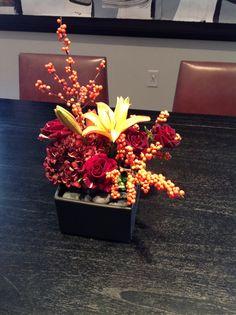 Fall arrangement of Merlot hydrangea, orange winter berry, yellow lily & rose.