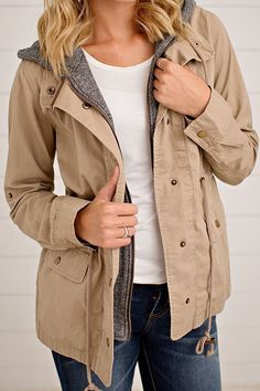 Beige utility jacket layered over a grey hoodie to stay cozy this winter!