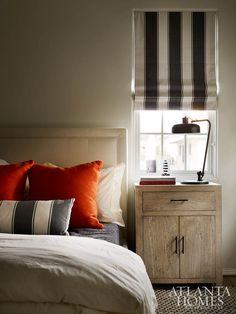 Deep orange pillows pop against this bedroom's otherwise neutral palette.