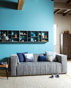 Living room with a bright blue wall and grey/hard coal vtwonen couch Lazy, Zuiver natural rug and accessoires by het Kabinet, Livv Lifestyle, Neef Louis, De Troubador, Loods 5, Nijhof, Bodilson and Six and Sons | Styling Kim van Rossenberg | Photographer Sjoerd Eickmans | vtwonen May 2015 | #vtwonencollectie