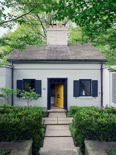 Painted brick cottage home exterior with black shutters and yellow front door