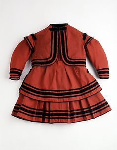 Child's red wool twill zouave ensemble with black trim, 1868-70.