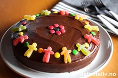 """""""Du, mitt hjertebarn, takk for at du fargelegger dagene mine i alle livets nyanser"""" (Ragnhild Bakke Waale). En myk og saftig sjokoladekake med masse deilig sjokoladekrem, som pyntes med seigmenn og Non Stop ...mmmm....ER ALLTID EN VINNER! Norwegian Food, Sweet Treats, Birthdays, Food And Drink, Birthday Cake, Pudding, Yummy Food, Sweets, Cookies"""