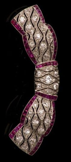 Art Deco ruby and diamond bow brooch with pierced design set with old cut diamonds and calibre cut ruby border with millegrain edging. www.vintageclothin.com