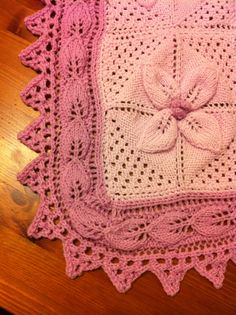 Pink knitted baby blanket with leaf and triangle edging